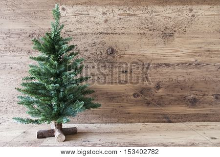 Christmas Card For Seasons Greetings With Copy Space. Green Christmas Tree With In The Front Of Aged Wooden Background. Rustic Or Retro Style.