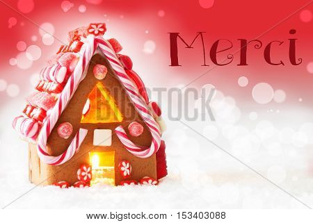 Gingerbread House In Snowy Scenery As Christmas Decoration. Candlelight For Romantic Atmosphere. Red Background With Bokeh Effect. French Text Merci Means Thank You