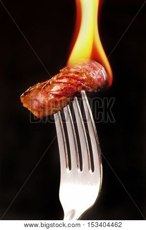 Flaming steak on a silver fork ready to eat.