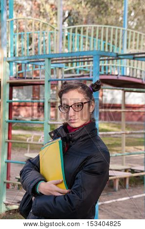 A student holding a notebook on the playground