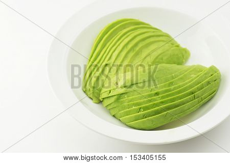Thinly cut slices of avocados on a white dish, on white background.