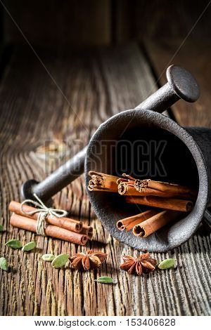Mortar with cinnamon anise and cardamom on old wooden table
