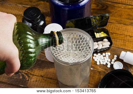 hand pouring water into a shaker. Sport and Fitness Supplement on a wood background