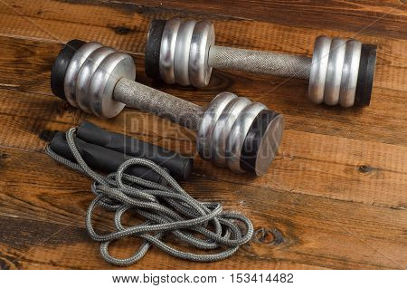 Athlete's set with, dumbbells and skipping rope on wooden background
