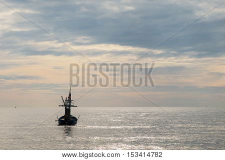 Fishing boat and the golden ocean sky background
