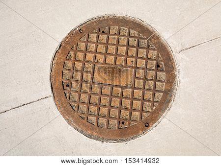 Cast iron manhole hatch on concrete pavement