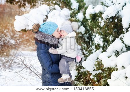 Mother and young daughter embracing in a winter park. Mother kissing daughter on the cheek. Happy family. Childhood and parenthood happiness. Close portrait.
