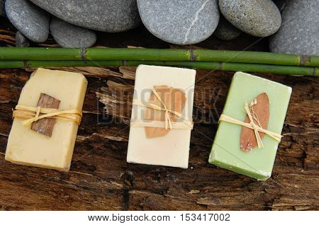 Three Soap closeup.with bamboo grove ,pile stones on old wood