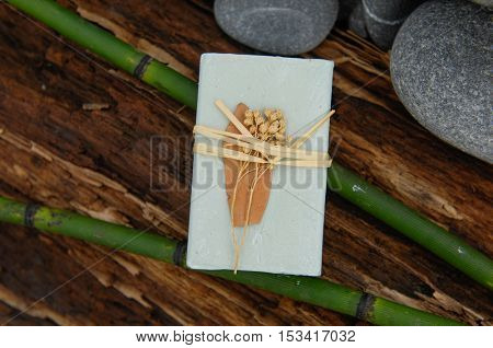 Soap closeup.with bamboo grove ,pile stones on old wood