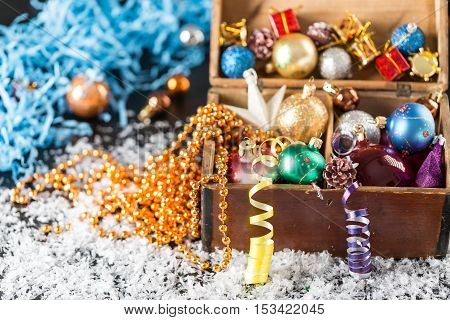 Colorful Christmas balls in a old wooden box on shiny background