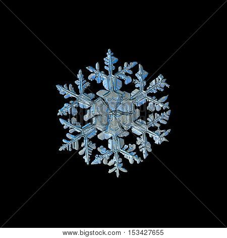 Snowflake isolated on black background: closeup photo of real snow crystal, captured on glass plate. This is large stellar dendrite snowflake with massive arms and central hexagon, divided by sectors.