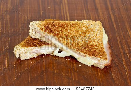 tasty melted toasted cheese and ham on a wooden cutting board