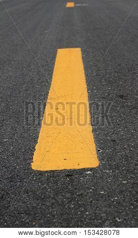 Close up road divide yellow line on asphalt
