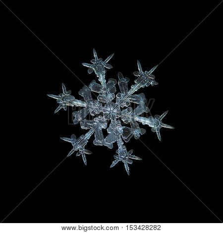Snowflake isolated on black background: macro photo of real snow crystal, captured on glass with LED back light. This is medium size snowflake of stellar dendrite type with sharp, ornate arms.