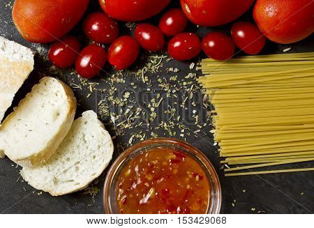 Italian food background with breadpastatomatoes and tomato spicy sauce