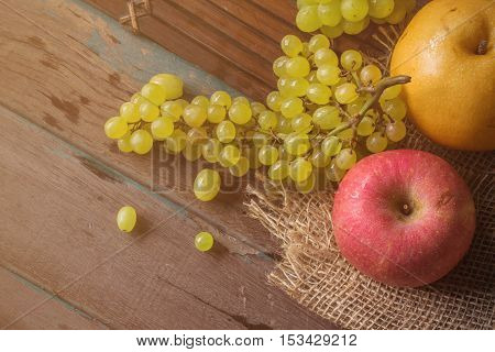Red apples and grapes on bamboo tray with cloth sacks on the wooden.