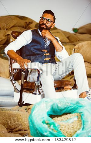 Portrait of bearded man in glasses on armchair against of textile bags with coffee beans