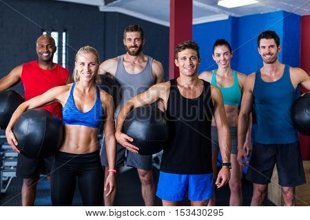 Portrait of smiling friends holding exercise ball while standing in gym