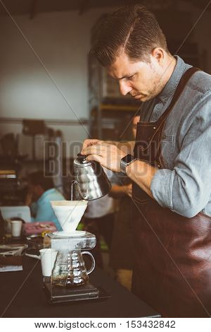 Portrait of professional coffeemaker pouring hot water in coffee machine