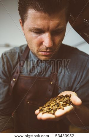 portrait of adult master of coffee looking down at roasted coffee beans in hand