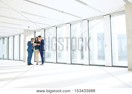 Full length of business people using digital tablet in empty office