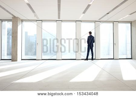 Rear view of young businessman looking through office window