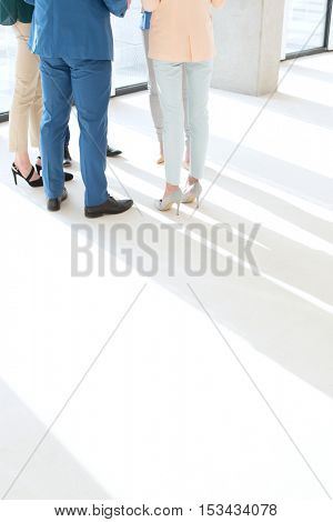 Low section of business people standing together in new office