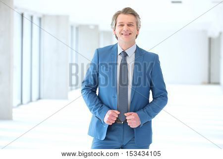 Portrait of smiling mature businessman standing in new office