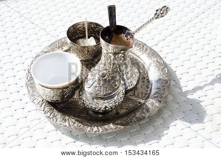 A metallic tray with copper plated cezve (džezva) filled with traditional foam Bosnian coffee a silver pot with turkish delight rahat lokum a clay cup and sugar cube pot served in an ornament Sarajevo set.