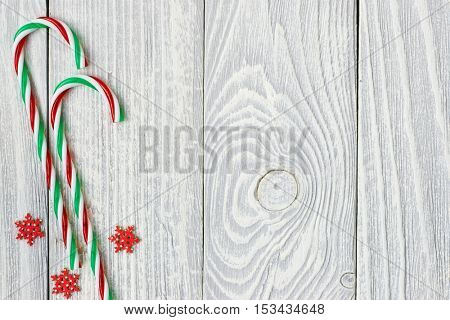 Christmas cane decoration on white wooden background
