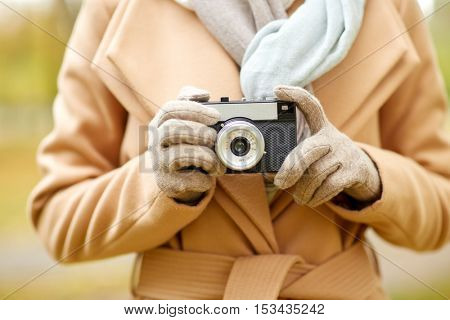 season, photography and people concept - close up of young woman taking picture with vintage camera in autumn park