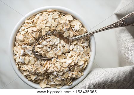 Dry rolled oatmeal in bowl with spoon. Top view.