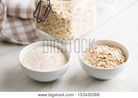 Dry rolled and ground oatmeal in bowls.