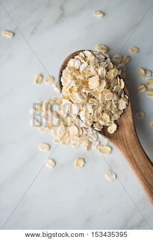 Dry rolled oatmeal in wooden spoon. Top view.
