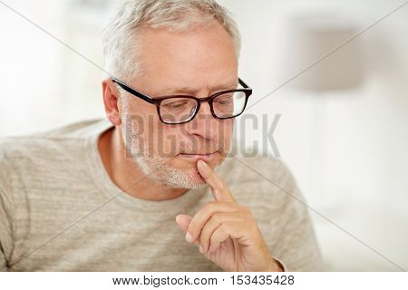 old age, problem and people concept - close up of senior man in glasses thinking