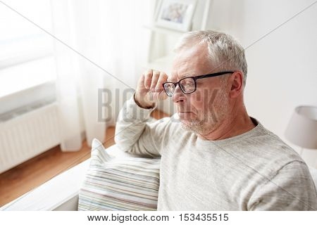 old age, problem and people concept -   senior man sitting on sofa at home and thinking
