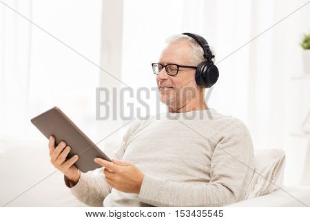 technology, people, lifestyle and distance learning concept - happy senior man with tablet pc computer and headphones listening to music at home