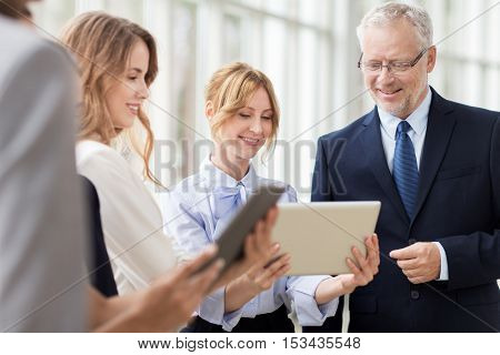 people, technology, work and corporate concept - business team with tablet pc computers at office