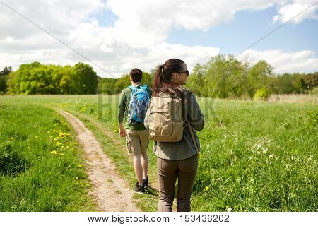 travel, hiking, backpacking, tourism and people concept - happy couple with backpacks walking along country road