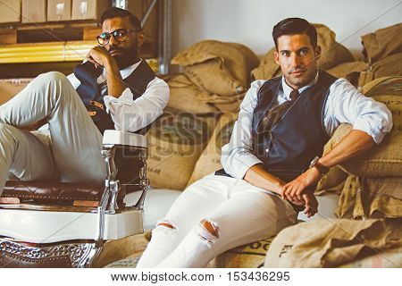Portrait of two handsome adult men sitting on bags full of coffee beans