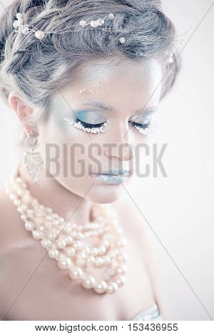 Winter Beauty Woman Fashion Model. Beautiful Girl with Snow Makeup and Hairstyle. Closed Eyes. New Year's Party Make-up