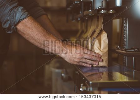 Unrecognizable male arms putting wrapped coffee beans in row