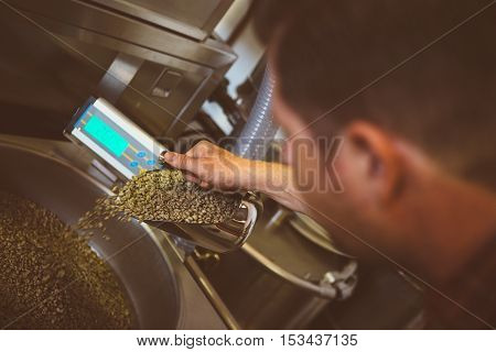 Close-up of unrecognizable professional filling roasting machine with scoop of raw coffee beans