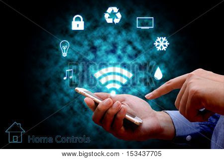 Man using smart phone or remote home control online home automation system.