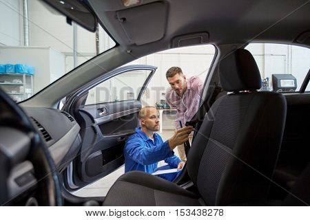 auto service, repair, maintenance and people concept - mechanic checking car seat belt with man or owner at workshop