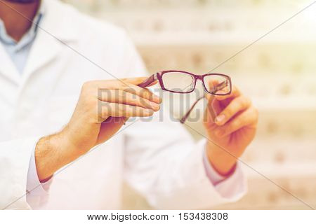 health care, people, eyesight and vision concept - close up of optician hands holding glasses at optics store
