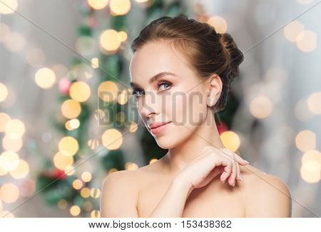beauty, people and winter holidays concept - beautiful young woman face over christmas tree lights background