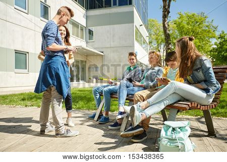 education, high school and people concept - group of happy teenage students with tablet pc computers sitting on bench at campus yard