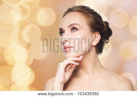 beauty, people and health concept - beautiful young woman touching her face over holidays lights background