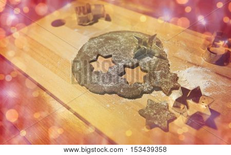 baking, cooking, christmas, holidays and food concept -  gingerbread dough and molds on wooden cutting board over lights
